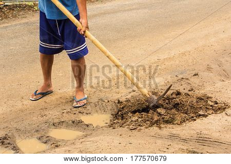 Man worker digging soil , asia style