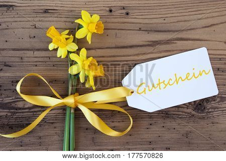 Label With German Text Gutschein Means Voucher. Yellow Spring Narcissus Or Daffodil With Ribbon. Aged, Rustic Wodden Background. Greeting Card For Spring Season