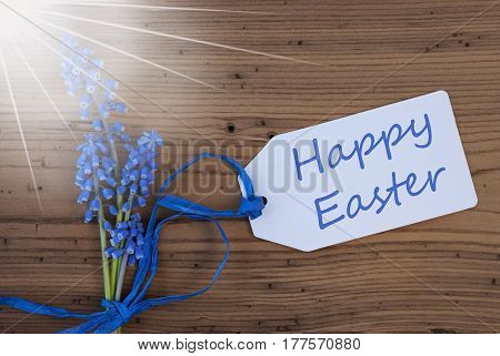 Label With English Text Happy Easter. Sunny Blue Spring Grape Hyacinth With Ribbon. Aged, Rustic Wodden Background. Greeting Card For Spring Season