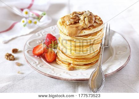 Pancakes with strawberries caramel cream and walnuts