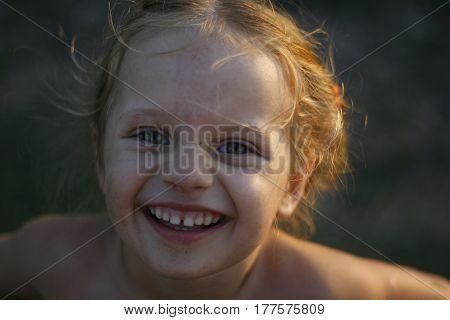 portrait of happy rustic grubby baby girl outdoors