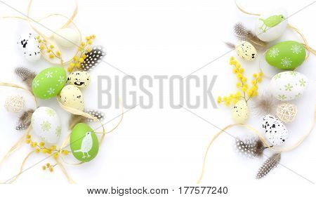 Easter Eggs And Mimosa Flowers On White Background With Space For Your Text. Top View.