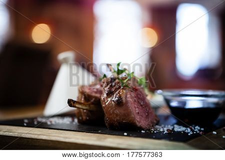 Close up of lamb chops with couscous and vegetables with a sauce of caramel and spices in a restaurant setting