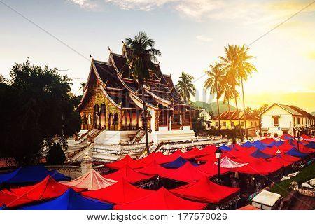Luang Prabang, Laos. Famous night market in Luang Prabang, Laos with illuminated temple and sunset sky