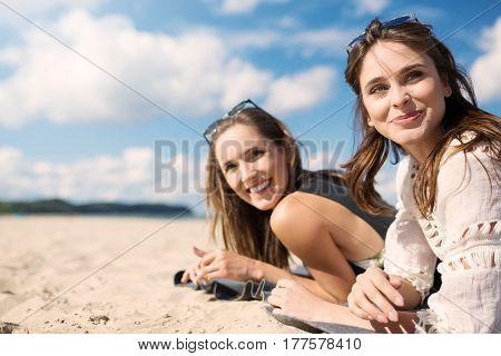 Beautiful Women Lying On Beach Laughing Looking Away