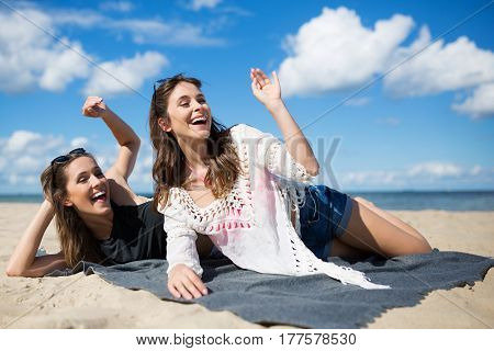 Two Young Women Lying On Beach Waving And Laughing