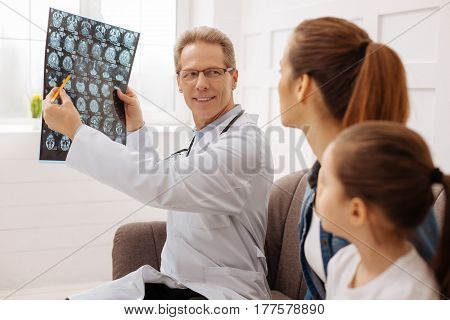 You made some progress. Experienced charming professional surgeon sharing some nice information with patients family while pointing something out on the x-ray picture he is holding