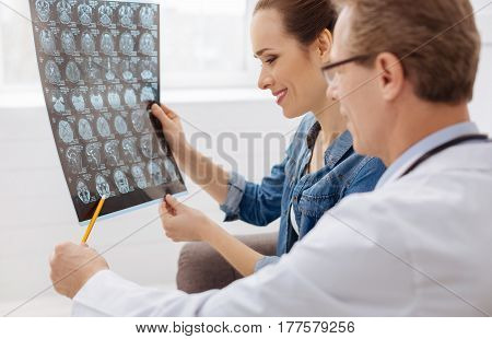Moving in the right direction. Delighted excellent experienced surgeon point at the brain scan shoving his patient her improvement while she paying a regular visit to him
