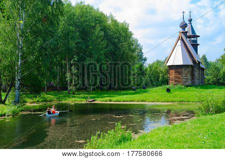 KOSTROMA RUSSIA - JULY 20 2016: Kostroma Architectural-Ethnographic and Landscape Museum-Reserve Kostromskaya Sloboda. Church of All-Merciful Savior on bank of river Igumenka. Unknown people ride boat