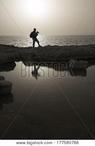 Photographer silhouette against sea landscape. Sunset time. Monochromatic image.