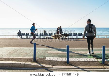 Nice, France - 25 February, People on the waterfront, 25 February, 2017. People and tourists having a rest on the Cote d'Azur.