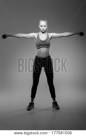 beautiful blonde girl in sportswear does exercises with dumbbells on a dark background