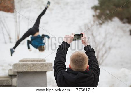 Teenager makes photo on smartphone of acrobatic jump girl in winter city park - parkour concept, de-focused
