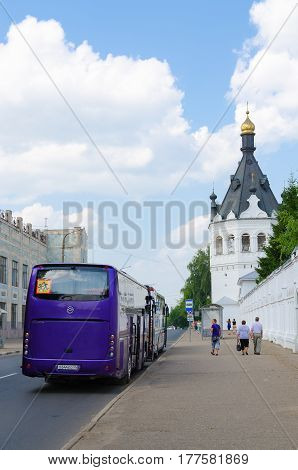 KOSTROMA RUSSIA - JULY 20 2016: Excursion bus near walls of Bogoyavlensko-Anastasiin Monastery Kostroma Russia. Unknown people walking down street