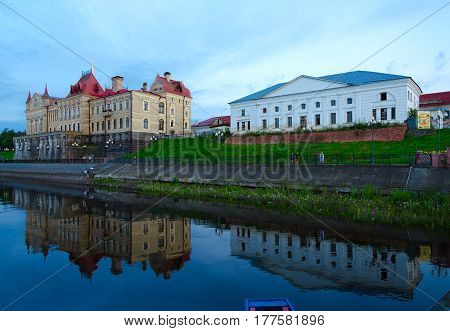 RYBINSK RUSSIA - JULY 21 2016: Buildings of former new and old (pilotage) grain exchange on embankment with reflection in water in evening Rybinsk Russia