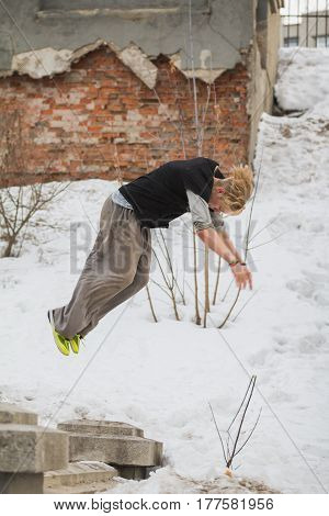 Free-run work out - teenager blonde hair guy training parkour jump flip in the snow covered park, telephoto
