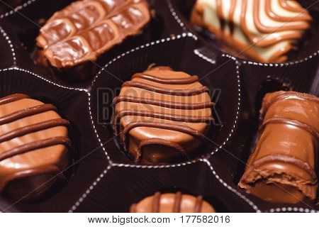 Close-up of variety chocolates in box. Assortment of sweet confectionery with chocolate candies and pralines
