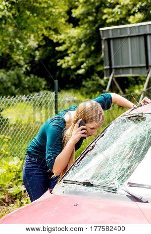 Woman dialing her phone after car crash