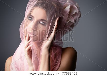 Portrait of a gorgeous young woman with bright make-up wearing a veil. Beauty, makeup and cosmetics concept.