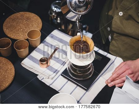 Hand Drip Coffee Barista pouring Hot water on coffee ground with filter Cafe restaurant