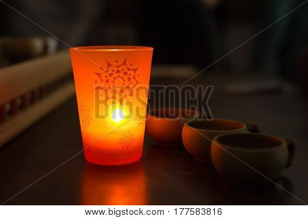 Chinese Tea cups and aromatic candle in the dark.