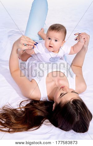 Happy young mother playing with her small baby. Family concept. Healthcare, pediatrics.