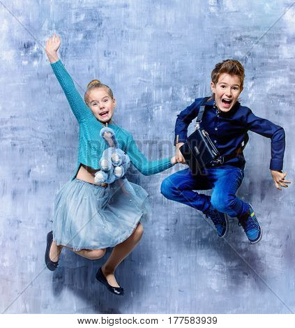 Kid's fashion. Two laughing children jumping for joy. Studio shot. Clothes for children.