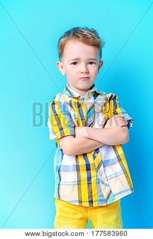 Portrait of a cute funny little boy looking at camera. Blue background. Copy space. Children fashion, summer concept.