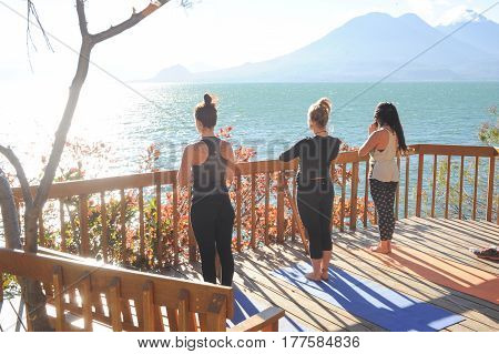 Young Girls Practicing Yoga With View Of Lake Atitlan