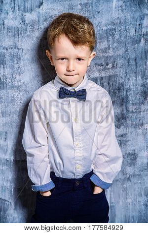Cute little boy in elegant clothes and a bow-tie. Kid's fashion.