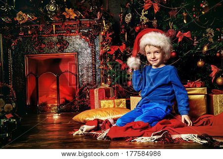 Christmas night. Little boy in pajama sitting near a Christmas tree waiting for Christmas and gifts.