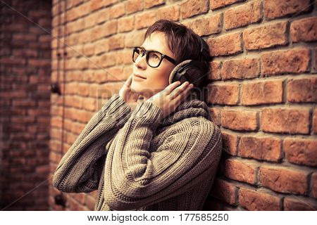 Happy young man listens to music in headphones at home. Radio music, DJ.
