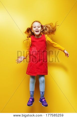 Happy five year old girl in bright summer clothes jumping for joy over yellow background. Happy childhood. Copy space.