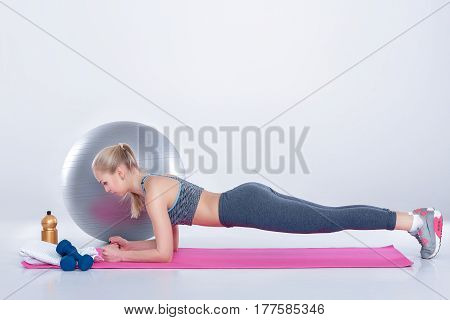 beautiful blonde girl in sportswear doing plank exercise on a fitness Mat on a gray background