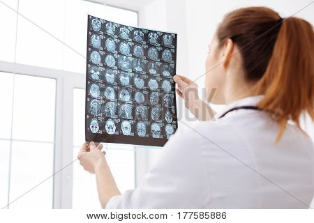 Many possibilities. Focused concerned trained neurosurgeon holding up and examining brain scans of the patient while working on his diagnosis