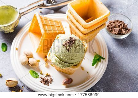 Pistachio ice cream in waffle cups on gray stone background. Homemade summer food concept. High angle view