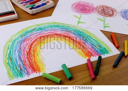 Drawing with pastel crayon. Crayon pieces and drawings on table. Hand drawn rainbow.