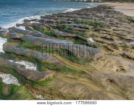 Rock formations at low tide on the ocean and a view of a nearby town