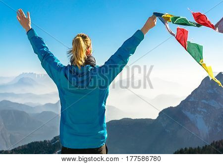 Happy celebrating winning success woman standing elated with arms raised up above her head in celebration of having reached mountain top holding tibetan prayer flags blowing in the wind. Reaching summit goal during hiking travel trek.