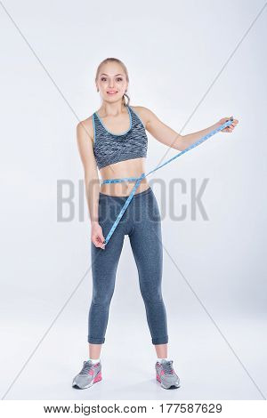 beautiful fitness girl in sportswear measures her waist with measuring tape on gray background