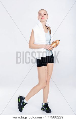 healthy sports woman in fitness clothes with gym towel and water bottle. soft light