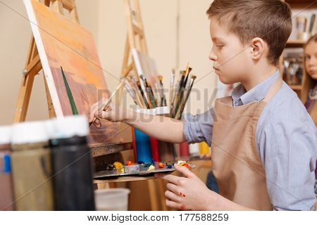 Full of concentration. Attentive talented young boy sitting in the art school and painting while demonstrating his talent and using pallet
