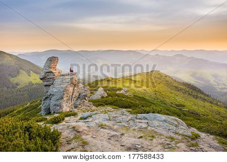man meditates in a lotus position on a rock in the mountains. mountain landscape. Lifestyle