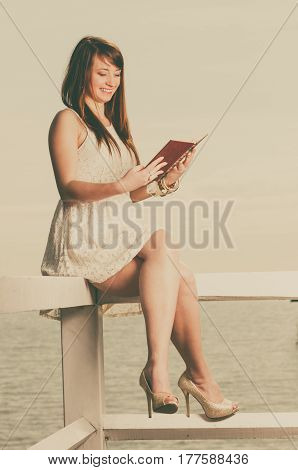 Books bookworm travel leisure time concept. Beautiful woman wearing white dress sitting on wooden hurdle near sea and reading book sepia