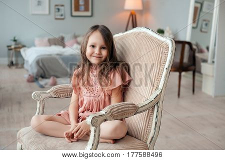 Portrait of a cute little girl sitting in the chair in her room. Childhood concept, indoor portrait.
