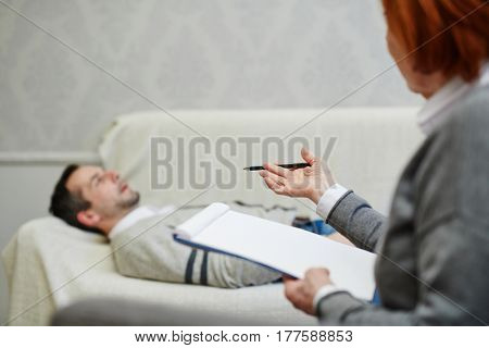Mature psychologist with clipboard looking at her middle-aged patient and giving him advice how to save his marriage