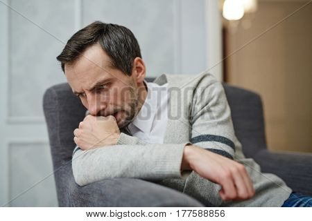 Nervous middle-aged man sitting on comfortable armchair and biting his nails while trying to find out problem solution