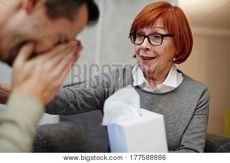 Portrait of crying middle-aged man having therapy session while his mature psychologist holding box with paper handkerchiefs in hand and trying to comfort him