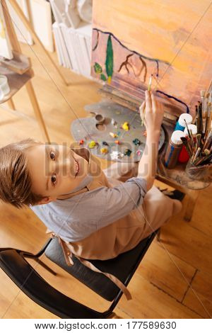 My first picture. Smiling positive cheerful boy sitting in the school and having art class while showing his abilities and painting