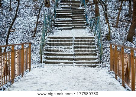 Staircase covered in snow in old abandoned park in winter